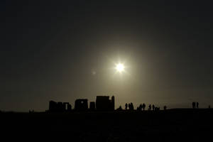 "photo - People are silhouetted as the sun rises above the ancient stone circle of Stonehenge, in southern England, as access to the site is given to druids, New Age followers and members of the public on the annual Winter Solstice, Friday, Dec. 21, 2012.  Doomsday hour is here and so still are we.  According to legend, the ancient Mayans' long-count calendar ends at midnight Thursday, ushering in the end of the world. Didn't happen.  ""This is not the end of the world. This is the beginning of the new world,"" Star Johnsen-Moser, an American seer, said at a gathering of hundreds of spiritualists at a convention center in the Yucatan city of Merida, an hour and a half from the Mayan ruins at Chichen Itza. (AP Photo/Matt Dunham)"