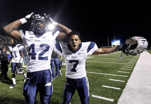 Photo - New Hampshire cornerback Jared Allison (7) and linebacker Akil Anderson (42) celebrate after winning an NCAA college football Division 1 championship quarterfinal game against Southeastern Louisiana in Hammond, La., Saturday, Dec. 14, 2013. New Hampshire won 20-17. (AP Photo/Jonathan Bachman)
