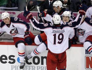 Photo - Columbus Blue Jackets players rush from the bench after a replay confirmed the sudden death winning shootout goal by Columbus Blue Jackets' Ryan Johansen (19) in an NHL hockey game against the Minnesota Wild, Saturday, March 15, 2014, in St. Paul, Minn. The Blue Jackets won 2-1. (AP Photo/Jim Mone)