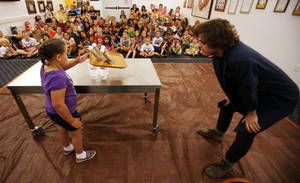 Photo - Grace Wilson, 6, attempts to knock away a tray with eggs sitting on it without harming the eggs while instructor Tyler Troy watches on during a June 13 Physics Funhouse event put on by the Metropolitan Library System and the Science Museum of Oklahoma at the Choctaw Library.  Photo by KT King, The Oklahoman <strong>KT King -  The Oklahoman </strong>