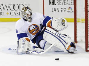 Photo - New York Islanders goalie Kevin Poulin (60) stops a shot on the goal during the second period of an NHL hockey game against the New York Rangers, Tuesday, Jan. 21, 2014, in New York. (AP Photo/Frank Franklin II)