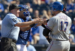 photo -   Home plate umpire Mike Everitt (57) steps between Kansas City Royals catcher Brayan Pena and Texas Rangers' Nelson Cruz (17) during the eighth inning of a baseball game at Kauffman Stadium in Kansas City, Mo., Monday, Sept. 3, 2012. Cruz was hit by a pitch on the play. (AP Photo/Orlin Wagner)