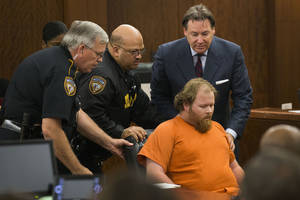 Photo - Ronald Lee Haskell collapses as he appears in court on Friday, July 11, 2014, in Houston.  Haskell, 33, is accused of killing his ex-wife's sister, Katie Stay, her husband and the children, ranging in age from 4 to 14, after binding and putting them face-down on the floor of their suburban Houston home. (AP Photo/Houston Chronicle, Brett Coomer, Pool)