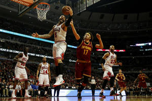 Photo - Chicago Bulls forward Carlos Boozer (5) gains control of the ball next to Cleveland Cavaliers center Anderson Varejao (17) during the first half of an NBA basketball game on Saturday, Dec. 21, 2013, in Chicago. (AP Photo/Andrew A. Nelles)