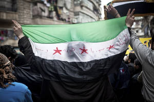Photo - A Syrian carries a revolution flag during a Friday protest in Aleppo, Syria, where young people and children sang songs against Bashar Assad and the Syrian regime, Friday, Dec. 21, 2012.(AP Photo/Virginie Nguyen Hoang)