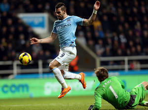 Photo - Manchester City's Alvaro Negredo, left, goes on to scores a goal past Newcastle United 's goalkeeper Tim Krul, right, during their English Premier League soccer match at St James' Park, Newcastle, England, Sunday, Jan. 12, 2014. (AP Photo/Scott Heppell)
