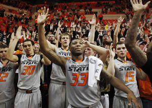 Photo - Oklahoma State players, led by guard Marcus Smart, sing the school's alma-mater after an NCAA college basketball game between Oklahoma State University (OSU) and Kansas State held in Gallagher-Iba Arena in Stillwater, Okla., Monday, March 3, 2014. Oklahoma State defeated Kansas State 77-61.  Photo by KT King/ For The Oklahoman