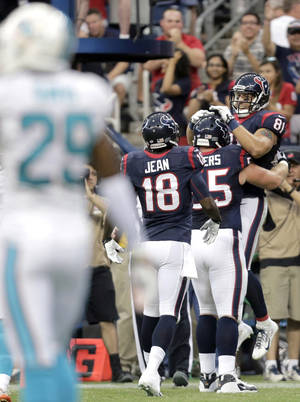 Photo - Houston Texans' Owen Daniels (81) celebrates his touchdown against the Miami Dolphins with Chris Myers (55) and Lestar Jean (18) as Dolphins' Will Davis (29) during the first half of a preseason NFL football game, Saturday, Aug. 17, 2013, in Houston. (AP Photo/Eric Gay)