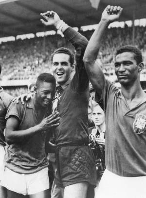 Photo - FILE - In this June 29, 1958 file photo Brazil's 17 year-old Pele, left, weeps on the shoulder of goalkeeper Gilmar Dos Santos Neves, after Brazil's 5-2 victory over Sweden in their World Cup final soccer match, in Stockholm, Sweden. Brazil's Didi is at right. On this day: Brazil wins it first World Cup with Pele scoring twice. (AP Photo/File)