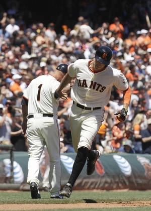 Photo - San Francisco Giants' Hunter Pence rounds the bases past third base coach Tim Flannery (1) after hitting a solo home run off of Minnesota Twins pitcher Ricky Nolasco during the third inning of a baseball game in San Francisco, Sunday, May 25, 2014. (AP Photo/Jeff Chiu)