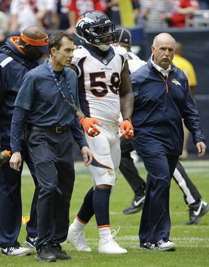Photo - Denver Broncos' Von Miller (58) is walked off the field after he was injured during the first quarter of an NFL football game against the Houston Texans, Sunday, Dec. 22, 2013, in Houston. (AP Photo/David J. Phillip)
