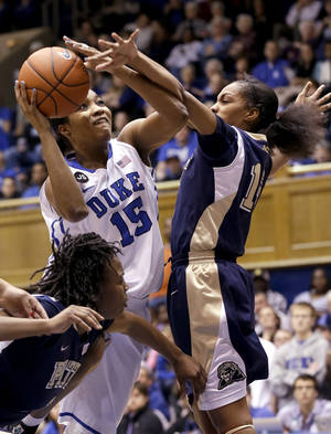 Photo - Duke's Richa Jackson (15) drives between Pittsburgh's Loliya Briggs, left, and Marquel Davis during the first half of an NCAA college basketball game in Durham, N.C., Sunday, Jan. 26, 2014. (AP Photo/Gerry Broome)