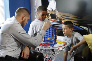 Photo - Oklahoma City Thunder's Cole Aldrich, left plays Connect 4 with Jaquay Wisby, 12, and Xavier Espinoza, 11, at the opening of the NBA Cares Learn & Play Center at the City Rescue Mission in Oklahoma City. Photo By Steve Gooch, The Oklahoman <strong>Steve Gooch - The Oklahoman</strong>