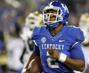 Photo - Kentucky's Jalen Whitlow runs for an 88-yard touchdown during the first quarter of an NCAA college football game against Alabama State, Saturday, Nov. 2, 2013, in Lexington, Ky. (AP Photo/James Crisp)