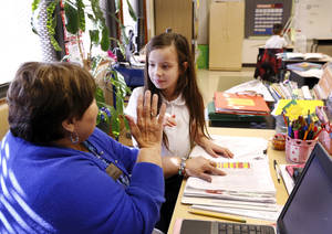 Photo - Ms. Lopez, second grade teacher at Rockwood Elementary School, raises her hand to exchange a high five with this student after she scored well on a reading exam  on Tuesday, Dec. 3, 2013. Photo by Jim Beckel, The Oklahoman Archives