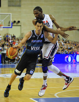 Photo - Pablo Prigioni, left, of Argentine senior national team drives past Carmelo Anthony of the U.S. during their pre-Olympic friendly basketball match at the Palau Sant Jordi in Barcelona, Spain, Sunday, July 22, 2012. (AP Photo/Manu Fernandez) ORG XMIT: MF116