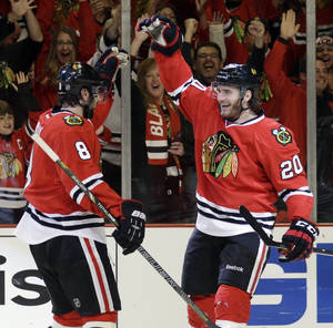 Photo - Chicago Blackhawks' Brandon Saad (20), right, celebrates with Nick Leddy (8) after scoring his goal during the second period in Game 2 of an NHL hockey second-round playoff series against the Minnesota Wild in Chicago, Sunday, May 4, 2014. (AP Photo/Nam Y. Huh)