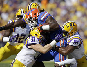 Photo - Florida running back Matt Jones is tackled by LSU linebacker D.J. Welter (31) and defensive end Danielle Hunter (94)in the first half of an NCAA college football game in Baton Rouge, La., Saturday, Oct. 12, 2013. (AP Photo/Gerald Herbert)