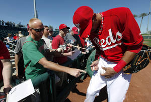 Photo - Cincinnati Reds' Billy Hamilton signs an autograph for a fan before an exhibition baseball game against the Seattle Mariners in Goodyear, Ariz., Monday, March 3, 2014. (AP Photo/Paul Sancya)