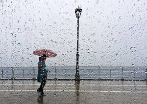 Photo - A Lebanese woman takes shelter under her umbrella as she walks on the Corniche, or waterfront promenade, in Beirut, Lebanon, Thursday May 8, 2014. Severe weather and heavy rains affected parts of the Middle East on Thursday including Israel, Jordan and Lebanon. Rains in Israel forced the evacuation of dozens of American tourists who were stranded overnight in a parking lot in the Negev desert, while a new refugee camp for Syrians was flooded in Jordan. (AP Photo/Hussein Malla)