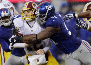 Photo - FILE - In this Dec. 29, 2013, file photo, New York Giants defensive end Justin Tuck, right, sacks Washington Redskins' Kirk Cousins (12) during the first half of an NFL football game in East Rutherford, N.J. Tuck signed with the Oakland Raiders. (AP Photo/Julio Cortez, File)