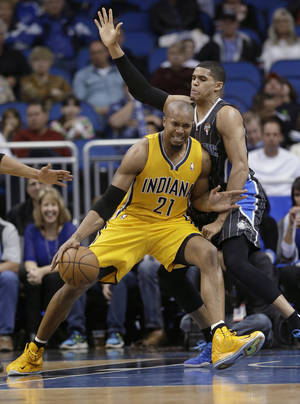 photo - Indiana Pacers' David West (21) make a move to the basket around Orlando Magic's Tobias Harris during the first half of an NBA basketball game, Friday, March 8, 2013, in Orlando, Fla. (AP Photo/John Raoux)