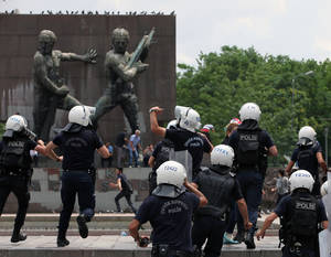 Photo - Police chase protesters as Turkish riot police spray water cannon at demonstrators who remained defiant after authorities evicted activists from an Istanbul park, making clear they are taking a hardline against attempts to rekindle protests that have shaken the country, in city's main Kizilay Square in Ankara, Turkey, Sunday, June 16, 2013.(AP Photo/Burhan Ozbilici)