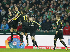 Photo - Dortmund's Robert Lewandowski of Poland, left, celebrates with teammates after scoring during the German first division Bundesliga soccer match between Werder Bremen and Borussia Dortmund in Bremen, Germany, Saturday, Feb. 8, 2014. (AP Photo/Frank Augstein)