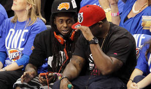 Photo - Rapper Lil Wayne sits courtside during Game 1 of the NBA Finals between the Oklahoma City Thunder and the Miami Heat Tuesday at Chesapeake Energy Arena in Oklahoma City.  Photo by Nate Billings, The Oklahoman