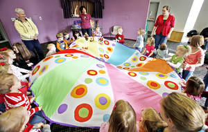 "Photo - Children bounce stuffed monkeys on a parachute in the ""Music with Susan"" class at Edmond Public Library. PHOTOS BY DAVID MCDANIEL, THE OKLAHOMAN"