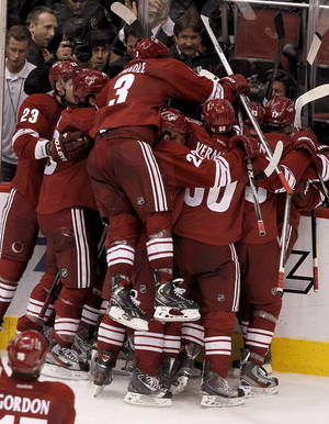 photo -   Phoenix Coyotes' Keith Yandle (3) leaps into the celebration as Oliver Ekman-Larsson (23), of Sweden, Daymond Langkow (22), Antoine Vermette (50), Adrian Aucoin (33) and Radim Vrbata (17), of the Czech Republic, surround Ray Whitney after his game-winning goal against the Nashville Predators during overtime of Game 1 in an NHL hockey Stanley Cup Western Conference semifinal playoff series, Friday, April 27, 2012, in Glendale, Ariz. The Coyotes won 4-3. (AP Photo/Ross D. Franklin)