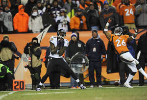 Photo - FILE - In this file photo from Jan. 12, 2013, Baltimore Ravens wide receiver Jacoby Jones, left, catches a pass for a touchdown despite the defense of Denver Broncos' Rahim Moore (26) late in the fourth quarter of an AFC divisional playoff NFL football game in Denver. (AP Photo/Jack Dempsey, file)