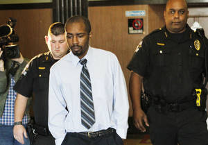 Photo - Christopher Travis Baker is taken Thursday from the courtroom at the Oklahoma County Courthouse in Oklahoma City. Photo By Steve Gooch, The Oklahoman