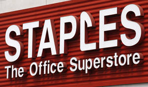Photo - FILE - In this May 17, 2011 file photo, a Staples sign is displayed on the front of a Staple store, in Portland, Ore. Staples says it will shutter 225 North American stores, about 10 percent of Staples Inc.'s worldwide total of 2,200, by the end of 2015, and the office-supply retailer has started a plan to save about $500 million annually. (AP Photo/Rick Bowmer, File)