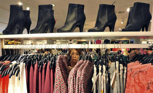 Photo - A woman shops at The Avenues Mall in Jacksonville, Fla. Economists say the gains in retail sales in August and September could bring stronger economic growth for the second half of the year. AP Photo