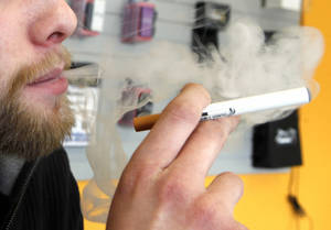 Photo - A sales associate demonstrates the use of a electronic cigarette and the smokelike vapor that comes from it in Aurora, Colo., on March 2, 2011. (AP Photo/Ed Andrieski) <strong>Ed Andrieski</strong>