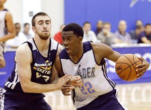 Photo - Oklahoma City Thunder's Semaj Christon (22) makes a move to get past Indiana Pacers' Jake Odum, left, during an NBA summer league basketball game in Orlando, Fla., Wednesday, July 9, 2014. (AP Photo/John Raoux)