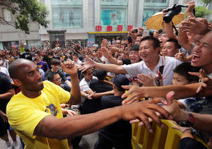 "Photo - FILE - In this Aug. 16, 2012 file photo, Los Angeles Lakers' Kobe Bryant, left, shakes hands with Chinese fans during a ""meet the fans"" event in Wuhan in central China's Hubei province. He has not uttered one word yet, Bryant's mere presence on a Twitter-like Chinese-language site has stirred plenty of excitement. Sina Weibo has verified that the NBA superstar has set up an individual account on its hugely popular microblogging site. Bryant's followers numbered more than 100,000 within hours on Thursday, Feb. 14, 2013, although no comments from Bryant had appeared. (AP Photo) CHINA OUT"