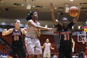 Photo - University of Houston forward Tyler Gilbert (33) passes the ball away from Louisville's Asia Taylor (31) and Sara Hammond (00) during the first half of an NCAA women's basketball game, Tuesday, Jan. 21, 2014, in Houston. (AP Photo/Patric Schneider)