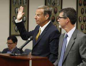 Photo - Former San Diego Mayor Bob Filner, left, stands with counsel in court and takes an oath before he pleads guilty on state charges of felony false imprisonment Tuesday, Oct. 15, 2013 in San Diego. Filner pleaded guilty to one criminal count of false imprisonment by violence, fraud, menace and deceit and two misdemeanor counts of battery. The charges involve three unnamed women victims. Filner, 71, resigned in late August, succumbing to intense pressure after at least 17 women brought lurid sexual harassment allegations. (AP Photo/UT-San Diego, John Gibbins, Pool)