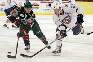 photo - Ryan Keller of the Oklahoma City Barons passes the puck past Joey Martin of the Houston Aeros during an AHL hockey game at the Cox Convention Center in Oklahoma City, Friday, Jan. 27, 2012. Photo by Bryan Terry, The Oklahoman