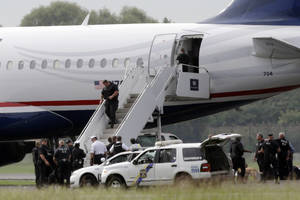 Photo -   Law enforcement officials work around a US Airways flight at Philadelphia International Airport, after the plane returned to the airport, Thursday, Sept. 6, 2012, in Philadelphia. A security scare that prompted authorities to recall an airborne U.S. flight was the result of an apparent hoax, police said Thursday. (AP Photo/Matt Rourke)