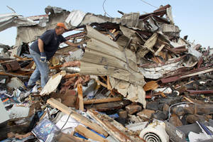 Photo - Matt Asbill digs through the wreckage of his  business. AP Photo