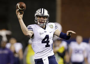 Photo - BYU quarterback Taysom Hill throws against Washington during first half of the Fight Hunger Bowl NCAA college football game Friday, Dec. 27, 2013, in San Francisco. (AP Photo/Marcio Jose Sanchez)