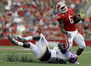 Photo - Wisconsin's Corey Clement tries to break away from Tennessee Tech's Malcolm Mitchell during the second half of an NCAA college football game Saturday, Sept. 7, 2013, in Madison, Wis. Wisconsin won 48-0. (AP Photo/Morry Gash)