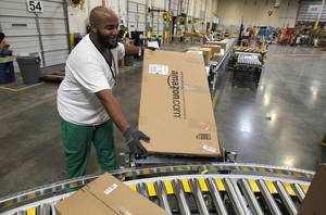 "Photo - FILE - In this Nov. 11, 2010 file photo, Leacroft Green places a package on the belt at an Amazon.com fulfillment center, in Goodyear, Ariz. Amazon is teaming up with the U.S. Postal Service to deliver packages on Sundays. The Seattle company said Monday, Nov. 11, 2013, that  Sunday delivery will be available this week to customers in the New York and Los Angeles metropolitan areas. Amazon and the Postal Service plan to roll out service to ""a large portion of the U.S. population"" next year, including Dallas, Houston, New Orleans, and Phoenix.  (AP Photo/Ross D. Franklin, File)"