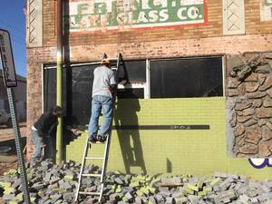Photo -  Green painted brick concealed the original cast stone and blond brick facade at 2415 N Walker Ave. The building is being renovated to become the home of Pizzeria Gusto, part of The Rise, an upscale shopping center in Uptown.  <strong> -  Provided </strong>