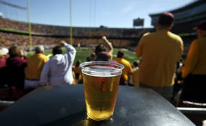 In this Sept. 8, 2012, photo, a beer sits atop a garbage can as Minnesota college football fans fans cheer a first quarter play against New Hampshire at TCF Bank Stadium in Minneapolis, Minn. A growing number of schools are capitalizing on fans' taste for the suds by bringing the party inside, opening taps in concourses that traditionally have been alcohol-free zones.(AP Photo/The Star Tribune, David Joles)  MANDATORY CREDIT; ST. PAUL PIONEER PRESS OUT; MAGS OUT; TWIN CITIES LOCAL TELEVISION OUT