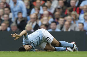 Photo -   Manchester City's Sergio Aguero reacts after a tackle from Southampton's Nathaniel Clyne during their English Premier League soccer match at The Etihad Stadium, Manchester, England, Sunday, Aug. 19, 2012. (AP Photo/Jon Super)