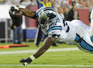 Photo - Carolina Panthers fullback Mike Tolbert dives over the goal line on a 3-yard touchdown pass play against the Tampa Bay Buccaneers during the second half of an NFL football game in Tampa, Fla., Thursday, Oct. 24, 2013. (AP Photo/Brian Blanco)